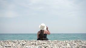 El turista de la muchacha se sienta en la playa y goza de la opinión, del agua y del sol hermosos del mar almacen de metraje de vídeo