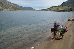 El turista de la muchacha se va en la arena cerca del lago de la montaña Imágenes de archivo libres de regalías