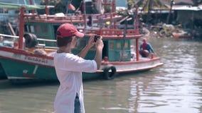 El turista de la muchacha tira los barcos de pesca en la opinión de la parte trasera del teléfono almacen de video