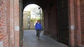 El turista de la mujer camina a través del arco de la casa almacen de metraje de vídeo