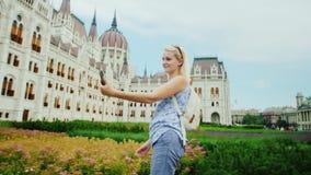El turista de la mujer joven da un paseo contra la perspectiva del parlamento húngaro, toma imágenes consigo misma por el teléfon almacen de metraje de vídeo