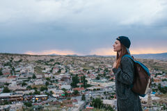El turista de la mujer joven se coloca en un fondo de la puesta del sol sobre la ciudad de Goreme en Turquía Cappadocia Turismo,  Fotos de archivo