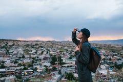 El turista de la mujer joven se coloca en un fondo de la puesta del sol sobre la ciudad de Goreme en Turquía Cappadocia Turismo,  Imágenes de archivo libres de regalías