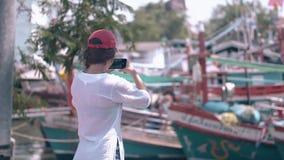 El turista de la mujer tira la bahía ilustrada con los barcos en el teléfono celular almacen de metraje de vídeo