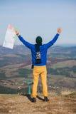El turista del hombre en montaña leyó el mapa Fotografía de archivo
