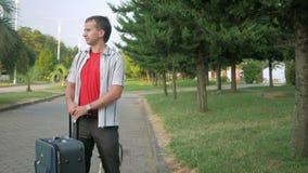 El turista del hombre joven está con una maleta grande en las ruedas alrededor del parque de la ciudad Él para y mira alrededor P almacen de metraje de vídeo