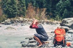 El turista del hombre joven restaura con agua en el río de la montaña Foto de archivo