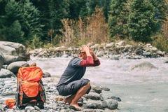 El turista del hombre joven restaura con agua en el río de la montaña Fotografía de archivo