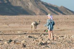 El turista del muchacho camina en un pueblo beduino con las puntillas del bastón en sus manos imagen de archivo libre de regalías