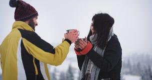 El turista dos consigue congelado en el lugar nevoso atractivo con el bosque y monta?a alrededor, intentan conseguir a bebida cal almacen de metraje de vídeo