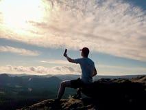 El turista en camiseta gris y gorra de béisbol roja toma las fotos Imagen de archivo