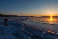 El turista en chaqueta roja está tomando un paisaje hermoso de la puesta del sol en el lago Baikal foto de archivo