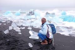 El turista en el hielo oscila en la playa negra de la arena en Islandia Fotos de archivo