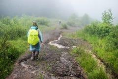 El turista en impermeable camina a la montaña en la niebla Fotos de archivo