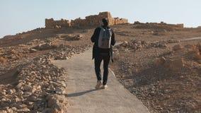 El turista europeo casual camina a las ruinas antiguas El hombre relajado en el camino del desierto del verano toma una foto del  metrajes
