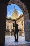 El turista europeo joven con una cámara toma una imagen en el Madrasa Bou Inania fotos de archivo