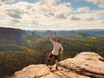 El turista feliz con la muleta del antebrazo sobre la cabeza alcanzó el pico de montaña Caminante con la rodilla quebrada en inmo imagenes de archivo