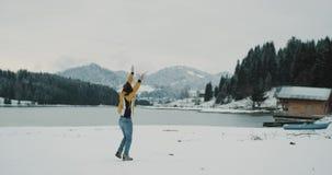 El turista feliz en el medio del lago y la montaña admiran toda la belleza de la naturaleza, visión asombrosa en invierno por otr almacen de metraje de vídeo