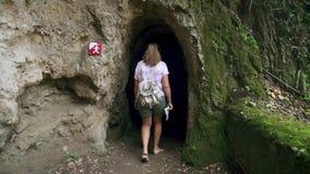 El turista femenino adulto está caminando solamente dentro de la cueva con las columnas C?mara lenta almacen de video