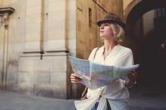 El turista femenino confuso con el atlas de la ubicación en manos no puede decidir adonde ir mientras que viaja Fotografía de archivo libre de regalías