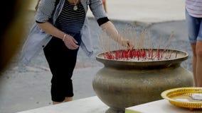El turista femenino está poniendo dos palillos del incienso al pote al aire libre en Asia almacen de video