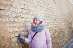 El turista femenino joven hermoso toca la pared de ladrillo antigua Fotos de archivo