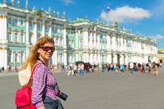 El turista femenino joven pasa el palacio del invierno en el santo Petersbur Imagenes de archivo