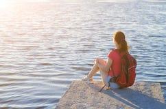 El turista femenino joven se está sentando al borde del embarcadero del río, a Imágenes de archivo libres de regalías