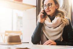 El turista femenino joven se está sentando en café en la tabla y está hablando en el teléfono celular La muchacha está llamando a Fotografía de archivo