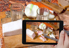 El turista fotografía la vodka, manteca de cerdo salada, cebolla fresca Fotografía de archivo libre de regalías