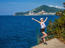 El turista hermoso de la muchacha aumentó sus manos para arriba El fondo de montañas y del océano Fotografía de archivo
