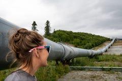 El turista joven de la hembra adulta admira la tubería de Alaska del transporte imágenes de archivo libres de regalías