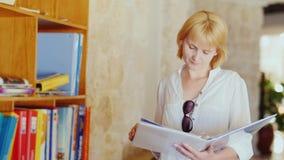 El turista lee un soporte del folleto informativo cerca del hotel almacen de metraje de vídeo
