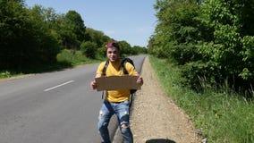 El turista loco en una camiseta amarilla está agitando una muestra y un funcionamiento a través del camino metrajes