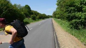 El turista loco en una camiseta amarilla está agitando una muestra y un funcionamiento a través del camino almacen de metraje de vídeo