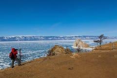 El turista masculino está tirando una foto de la roca del chamán en la isla de Olkhon imagen de archivo
