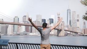 El turista masculino feliz sube al horizonte épico de la cerca de la orilla del río del puente de Brooklyn en New York City, aume almacen de video