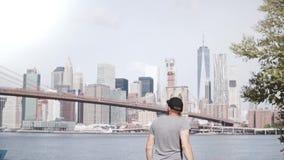 El turista masculino feliz sube al horizonte famoso de Nueva York en la cerca de la orilla del río del puente de Brooklyn, sintie almacen de metraje de vídeo