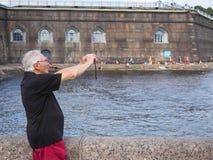 El turista masculino que toma las imágenes de las vistas y hace un selfie en el verano St Petersburg Fortaleza de Peter y de Paul imagen de archivo