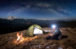 El turista masculino tiene un resto en su campo en la noche debajo del cielo hermoso por completo de estrellas y de la vía láctea fotografía de archivo