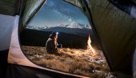 El turista masculino tiene un resto en el suyo que acampa en las montañas en la noche debajo del cielo nocturno hermoso por compl imagen de archivo