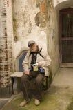 El turista mayor se sienta en un banco Fotografía de archivo libre de regalías