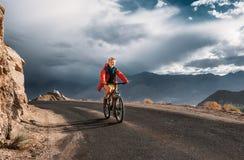 El turista monta la bici en el camino en la montaña de Himalaya Imagen de archivo