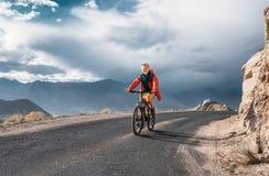 El turista monta la bici en el camino en la montaña de Himalaya Fotos de archivo