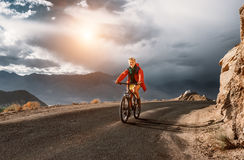 El turista monta la bici en el camino en la montaña de Himalaya Fotografía de archivo