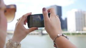 El turista moreno hermoso filma una ciudad con su smartphone almacen de video