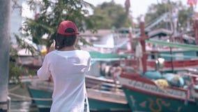 El turista moreno toma las fotos de barcos contra árboles verdes almacen de video
