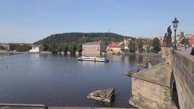 El turista que camina en Charles Bridge icónico y el río barge en curso en el río de Moldava almacen de metraje de vídeo