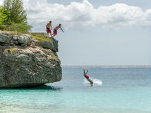 El turista que salta de la roca en la playa magnífica de Knip Imagenes de archivo