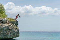 El turista que salta de la roca en la playa magnífica de Knip Fotos de archivo